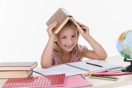 Kind hält Buch übern Kopf beim Lernen